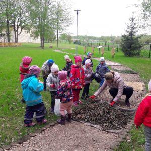 Kopā ar bērniem palīdzam izveidot sajūtu taku, salasot zariņus skolas parkā.